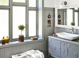 PERSONLIG PREG PÅ BADET: Store vinduer uten gardiner gir mye lys til badet. Vindusfolie hindrer innsyn. Medisinflasker og en grønn plante i vinduet er enkel pynt og gir badet en landlig følelse. Linhåndklær i gammeldags mønster og et lite hjerte av lavendel er en detalj som blir lagt merke til.