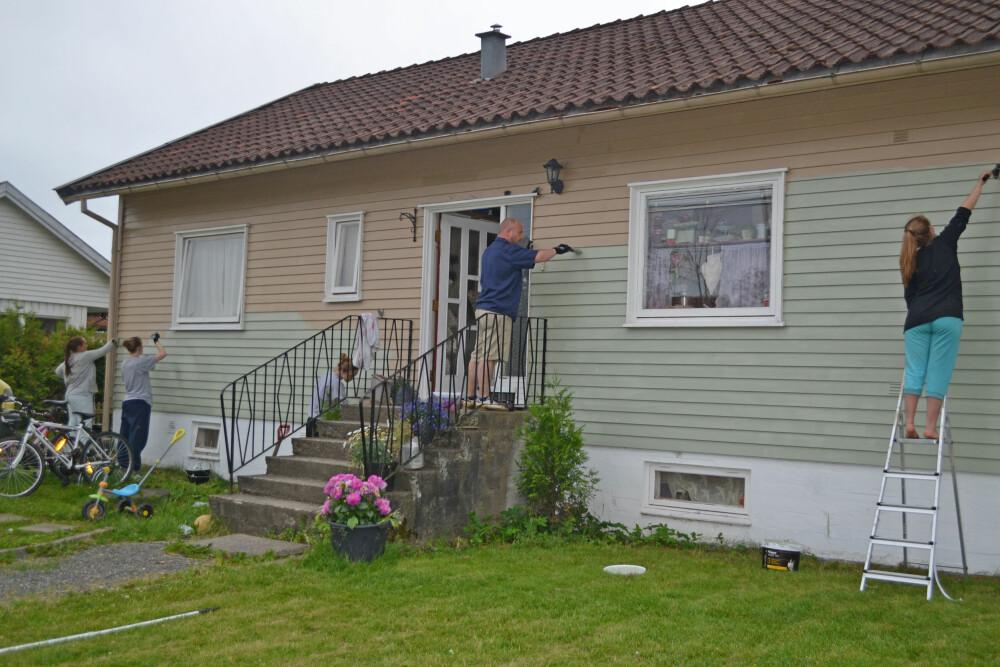 TIL VERKS: Her er datteren Silje (t.h.), Dan Richard (i midten) og tre familievenner i gang med å male huset i den grønne fargen familien valgte til slutt.