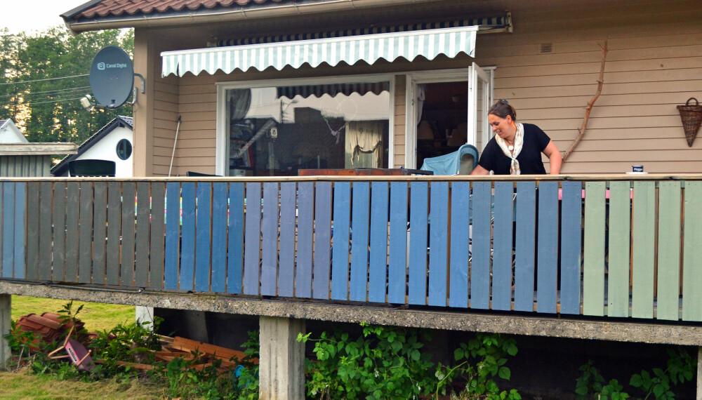 MALE HUS: Familien Hagen testet totalt ti fargeprøver på veggen og rekkverket før de valgte fargen på huset. Det ble, ironisk nok, ingen av de som var testet. Her er Linda Hagen på den fargerike terrassen.