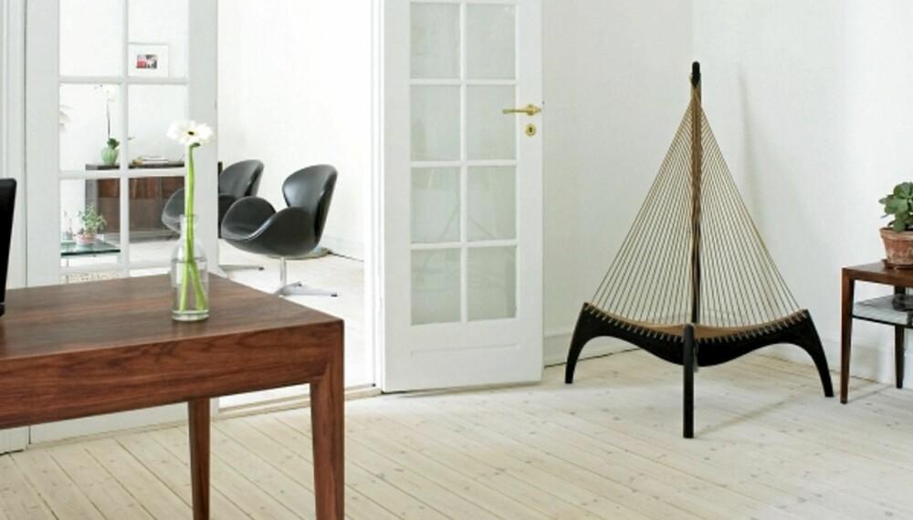 """KJØLIG ELEGANSE: Lutede nåletregulv, hvite vegger og moderne danske klassikere i palisander er typiske trekk. Stolen """"Harpen"""" er deisnget av Jørgen Høvelskov."""