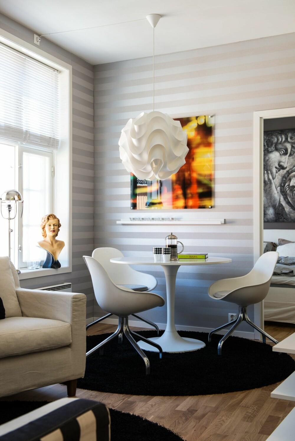 RUND SPISEPLASS: Rundt bord og rundt gulvteppe svekker inntrykket av leilighetens skjeve vinkler. Bord og stoler er fra Ikea, men kjøpt brukt på Finn. Tapetet er fra Borge. Fotografiet er egenprodusert. Pendelen fra Le Klint er kjøpt på Ruths Design.