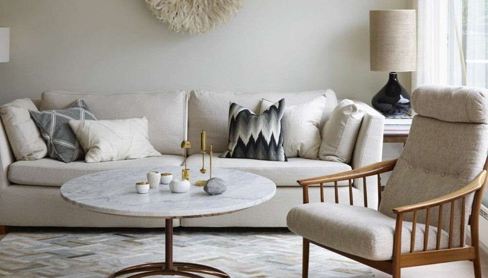 LYSE NYANSER: Stuebordet er laget av understellet fra et gammelt bord og en ny marmorplate fra Mina Milanda. Lenestolen er kjøpt brukt, og hadde opprinnelig mørkegrønt, storblomstret trekk. Sofa fra Ikea med svartmønstret pute fra Milla Boutique. og bak t.h. en linpute fra Bolina. Veggdekorasjonen i fjær er en afrikansk hatt fra Anouska. Lampe t.h. fra Eske og lampe t.v. et bruktfunn. Teppe fra Zara Home. Hvite telysholdere og diamantformet dekorasjonsstein, alt fra Milla Boutique.
