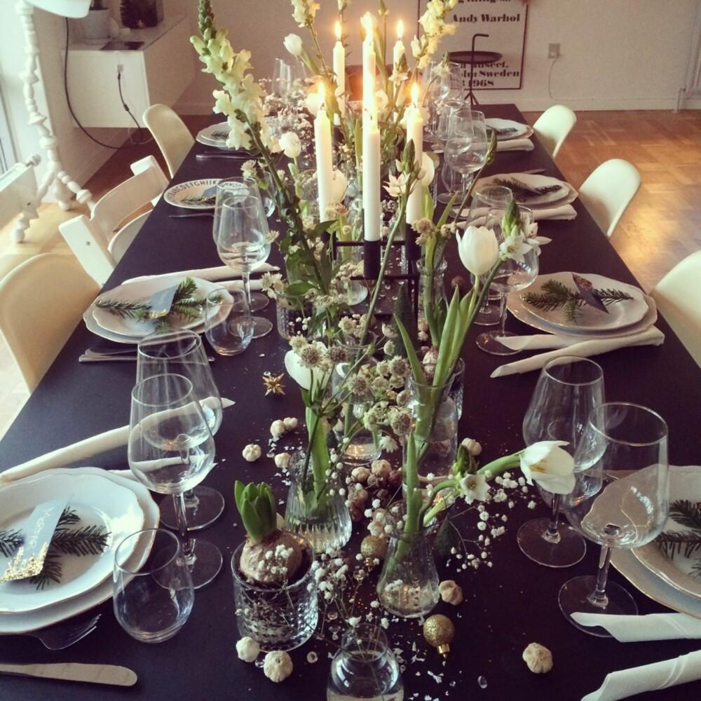 SORT OG HVITT: Instagrammer Camilla Hamiltorn dekket fjorårets julebord med svart duk og hvite blomster. På bordet har hun strødd kongler, hvitløk og glitter. Tallerkenene er pyntet med granbar og hjemmelagede bordkort.
