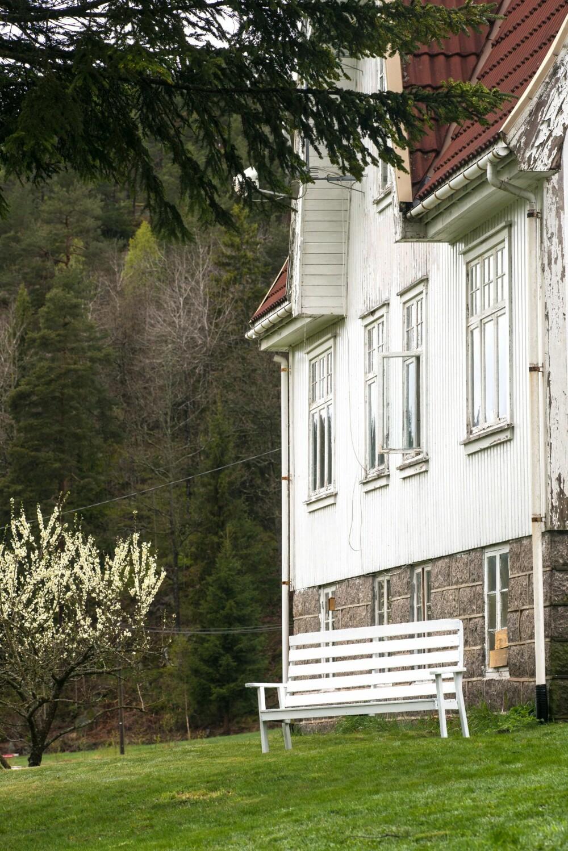SNART FERDIG MALT: Det hvite, store huset har en spesielt flott grunnmur av granitt. Snart er det ferdig malt og klart for sommeren.