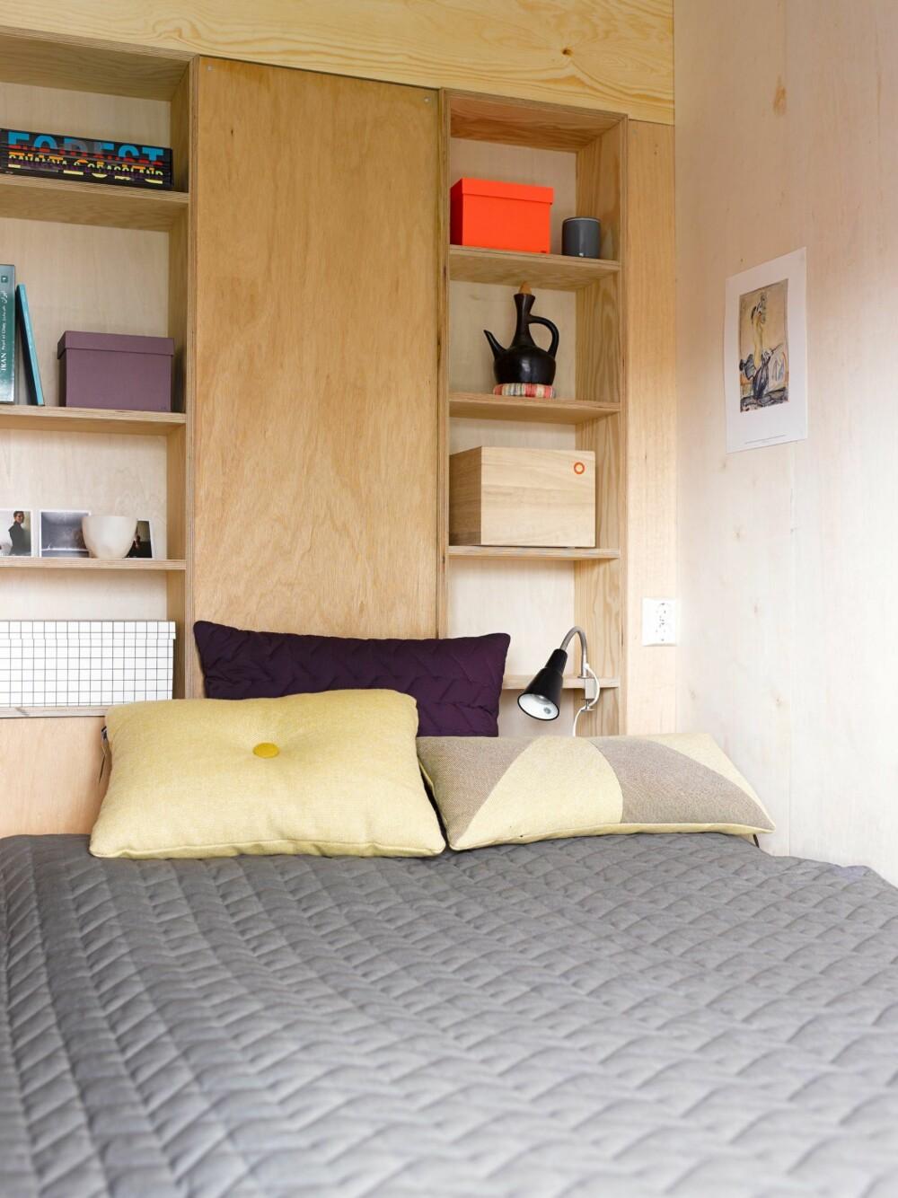 SPESIALTILPASSET: Hyllene på soverommet er bygd rundt et rør. Teppet og putene er fra Hay.