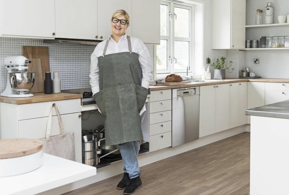 Holder stand. Ikea-kjøkkenet var nytt i 2000 og gjør jobben den dag i dag, selv om et helt nytt kjøkken står på Trudes ønskeliste. I sprutsonen er det valgt hvite glassmosaikk-fliser. Det grå forkleet i grov kanvas kommer fra Uashmama.