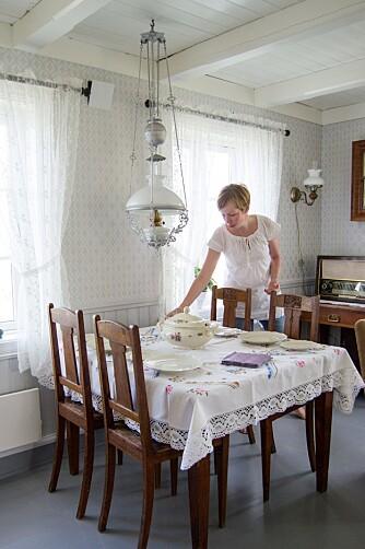 STO I HUSET: Spisebordet og den flotte lampa er noen av tingene som var i huset da Hilde og Rune tok over, og som nå er blitt en del av den fine helheten som paret har skapt i huset. Her dekker Hilde bordet med nydelig gammelt porselen.