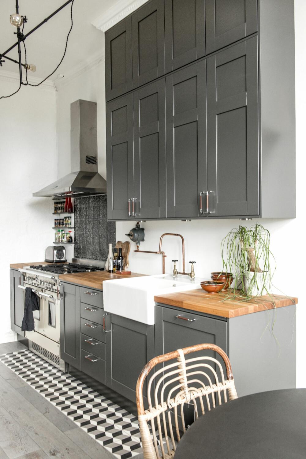 KJØKKENET: Kjøkkeninnredningen er fra Ballingslöv, benkeplaten fra Ikea, vasken fra Villeroy & Boch og viften fra Falcon.  Krydderhyllen er laget av avkappede plankebiter. Metallflisene under viften er fra Palma.