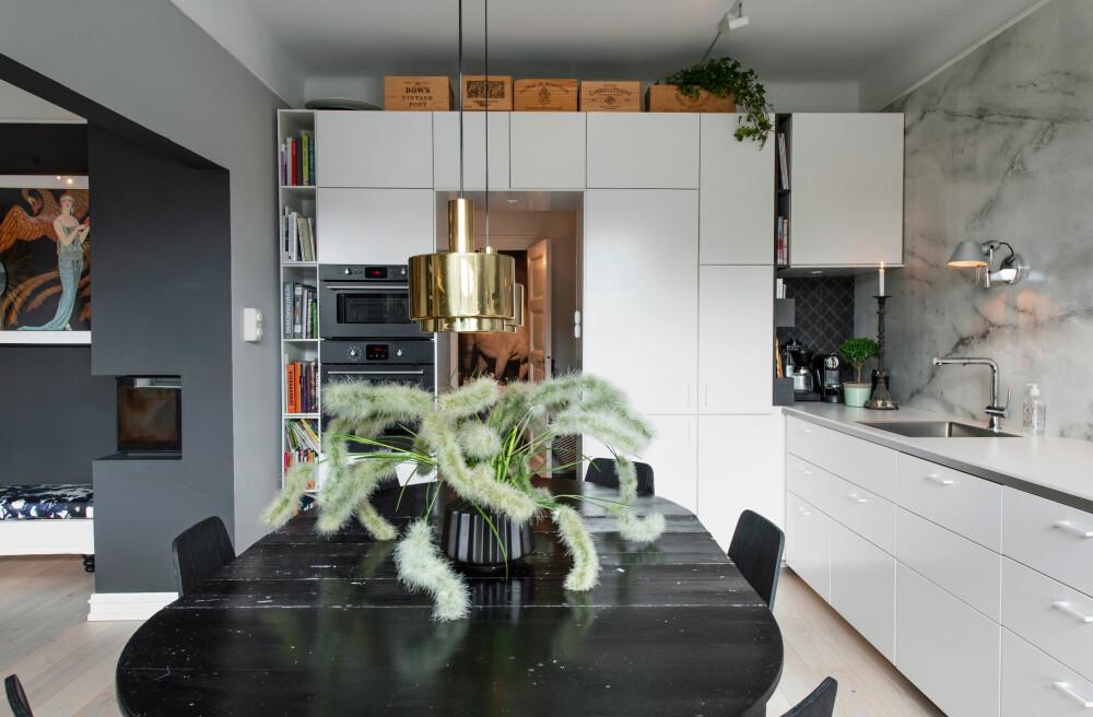 STILBRUDD: Spisebordet kan gjerne bryte med kjøkkeninnredningen, og sprutsonen kan gå helt opp til veggen. Legg merke til de åpne hyllene og vegglampen i sprutsonen.