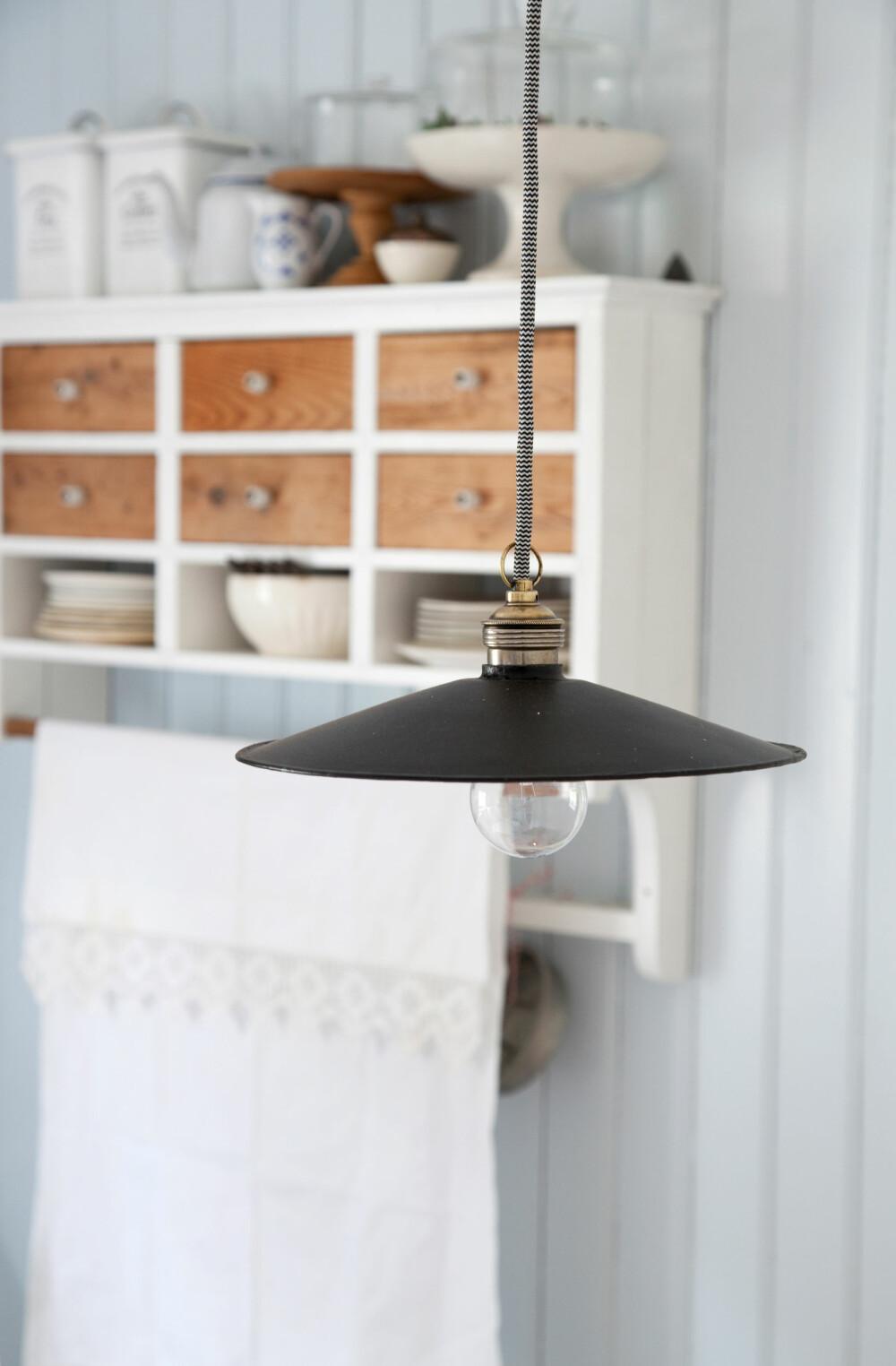ENKELT: En enkel skomakerlampe med messingtopp og tekstilledning henger over kjøkkenbordet.
