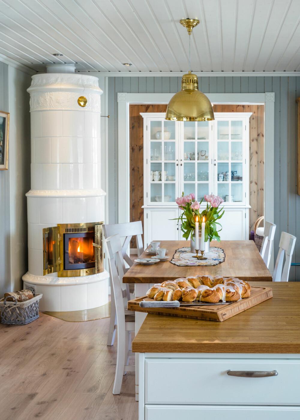 SMYKKET: Den staselige kakkelovnen er en ekstra trivselsfaktor på kjøkkenet, der den står sentralt plassert og sprer varme ut i hele huset.