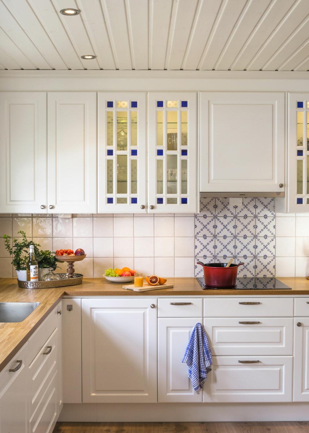 KONTRASTER: To forskjellige fliser er brukt i sprutsonen. Bak ovnen valgte paret blå og hvite fliser, for å bryte opp litt i alt det hvite. Blåfargen går igjen i glassdørene.