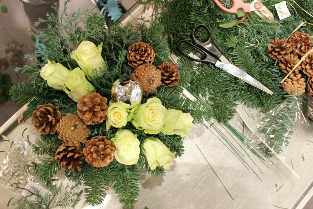 NESTEN FERDIG: Etter å ha laget deg punkter med roser, kongler og eventuelle julekuler, fyller du de resterende hullene med krysantemum eller brudeslør. Oasisen skal ikke synes.