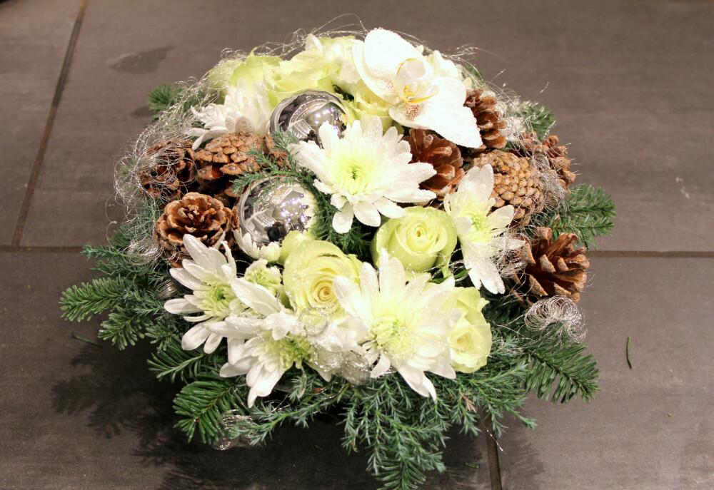 FERDIG: Denne vakre blomsterdekorasjonen laget Christine Kadic hos Mester Grønn. Hun brukte granbar, sypress, hvite roser, hvite krysantemum, kongler, julekuler og en orkidéblomst. Ekstra fint resultat får du, dersom du surrer litt englehår rundt blomstene til slutt.