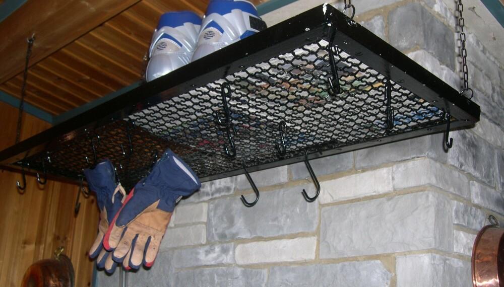 TØRKE KLÆR PÅ HYTTA: Tørkerist i smijern som kan henge over vedovnen, er praktisk med tanke på både sko og klær. Kjettingen kuttes ved å åpne et ledd med to tenger, og den henges i taket ved hjelp av kroker. En slik rist kan kjøpes i flere hyttebutikker. Kr 990, hyttelivsenteret.no Foto: Privat
