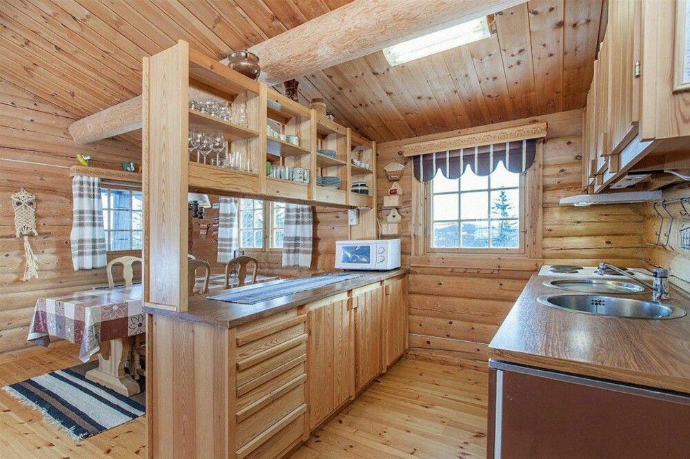 Før: Et enkelt hyttekjøkken med skillevegg mot spiseplassen.