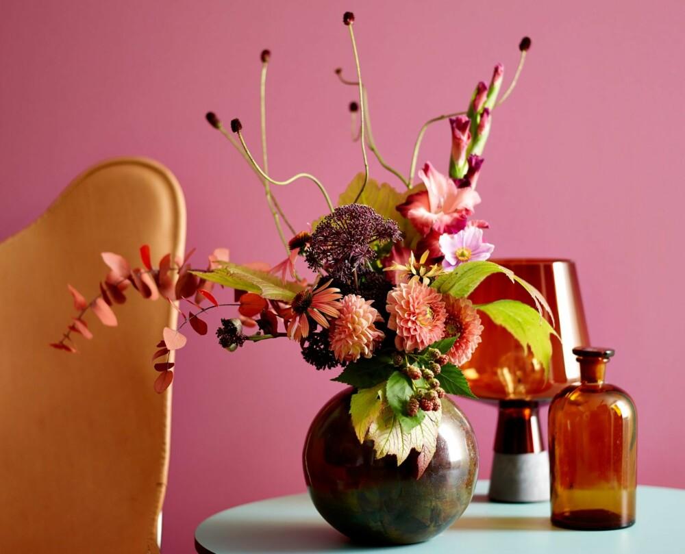 FARGERIKE BLOMSTER: Et supert triks om du ikke er like vågal og går for rosa farger i stuen, er å friske opp hjemmet med fargerike blomster. - Jeg elsker blomster! Det deilige er at de kan settes sammen i alle varianter. Til jul hadde jeg oransje roser og kongler. Sammen med den oransjee kanten på serviset ble det akkurat passe jul. (Farge: St. Paulia FR 2504.)