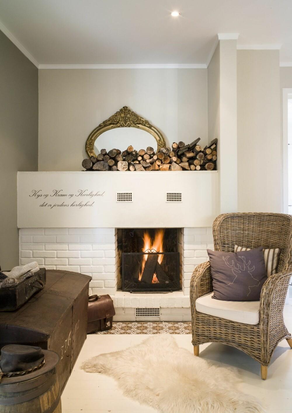 LUN KROK: I den lyse  hallen har paret laget en koselig peis. Saueskinn og kurvstol er med på å skape en lun og god atmosfære i rommet. For å beskytte gulvet foran peisen er det benyttet betongfliser fra Ulfven.