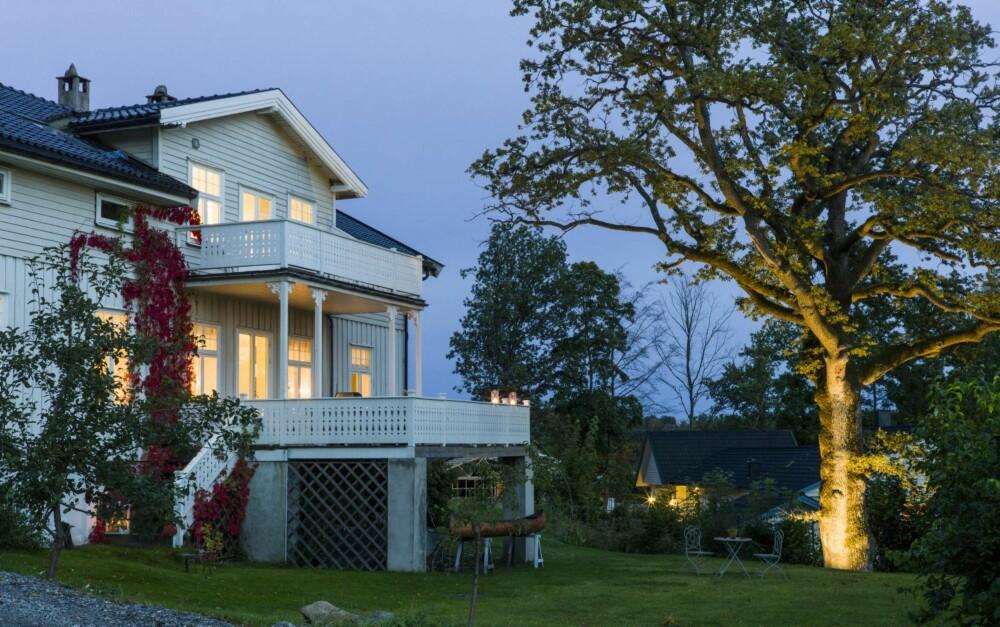 STEMNING OG HISTORISK SUS: Ulfven-huset lyser vakkert opp i skumringen. En villvin gir farge til fasaden, og den stolte eika har også fått belysning.