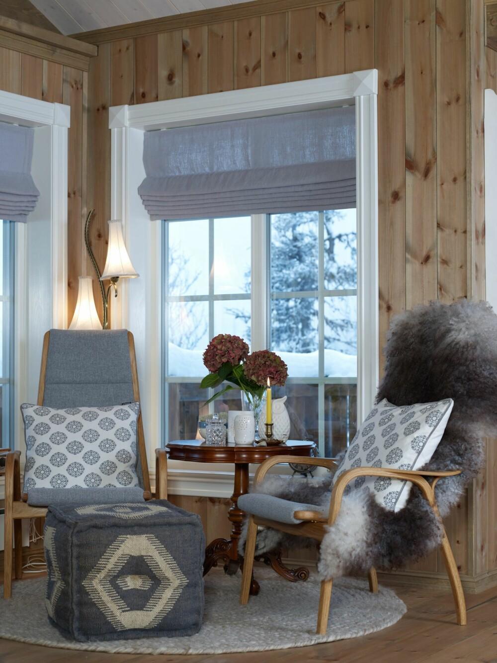FAVORITTSTED: Lesekroken ved vinduet er Sarahs favorittplass. Den er møblert med to av de stilrene stolene Lamino fra Swedese, design Yngve Ekstrøm, trukket i et grått ullstoff. Bak dem står en særegen lampe, som er arvet etter Sarahs mormor. Puffen er kjøpt på Kremmerhuset, gulvteppe og gardinstoff er fra Home & Cottage. De mange skinnfellene i hytta er kjøpt på Oppland Bygg og Anleggs interiørutsalg. Det runde søylebordet er arvet.  (FOTO: Inger Mette Meling Kostveit)