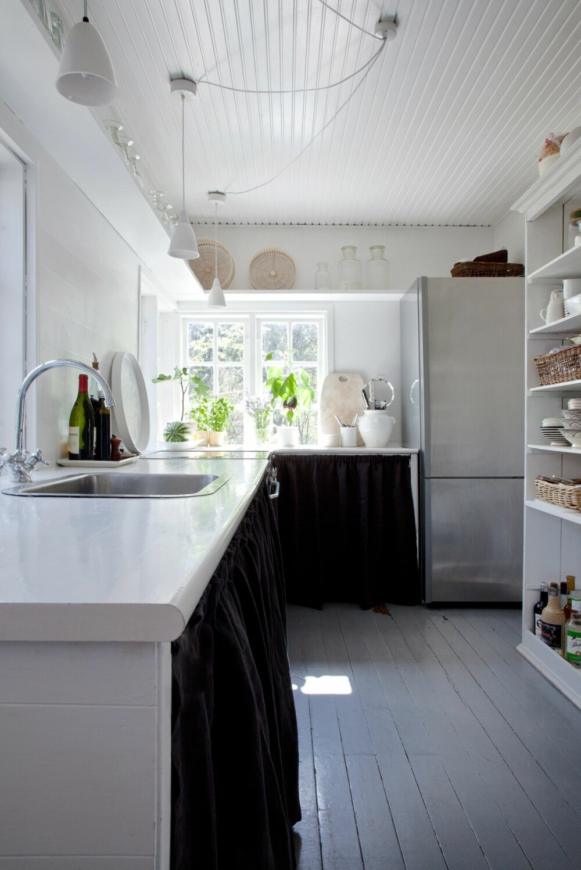 ROMANTISK: Kjøkkenet er innredet som et typisk spartansk sommerhuskjøkken fra 50-tallet. Et forheng skjuler matvarene, og glass og mugger står på en hylle over vinduet. Både Karen og Tine er glade i å jobbe på kjøkkenet, så komfyren, ovnen og kjøleskap er i dagens standard. Den åpne reolen rommer tallerkener, skåler, bestikk, samt krydder, oljer og eddik.