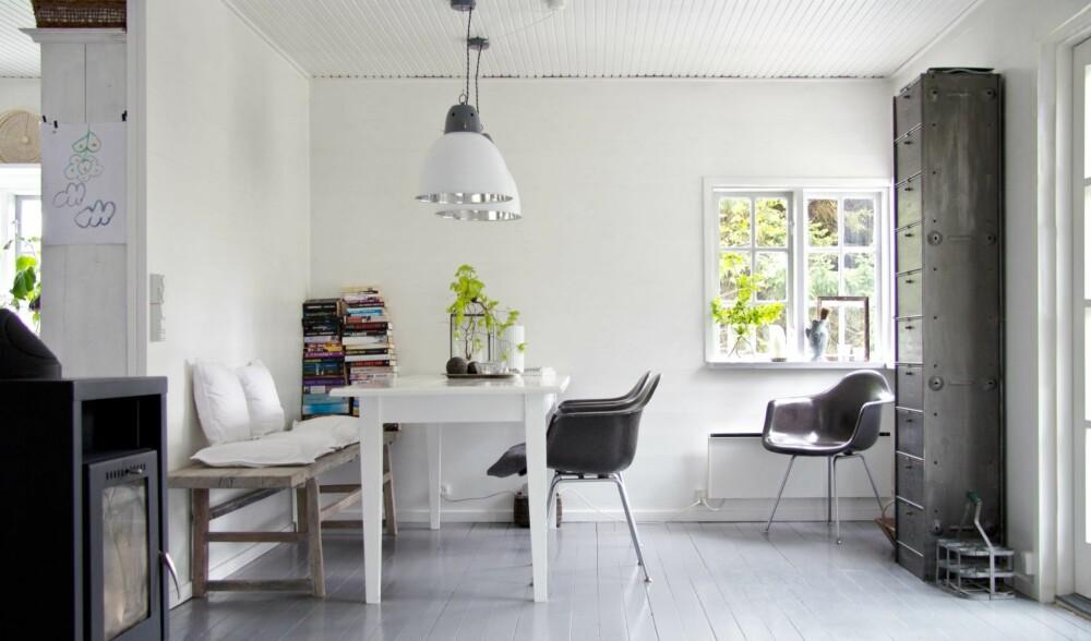 HVITT OG GRÅTT: Spisestuen er enkel, men elegant. Veggene og gulvet er som resten av huset malt i hvitt og grått. Spisebordet er malt høyglanset hvitt, og bondebrisken med puter er komfortabel. De antrasittgrå stolene fra Eames står i fin kontrast til benken, det samme gjør det høye metallskapet og fabrikklampene. Husets bibliotek er uhøytidelig stablet ved enden av benken, og er det eneste fargeinnslaget i rommet.