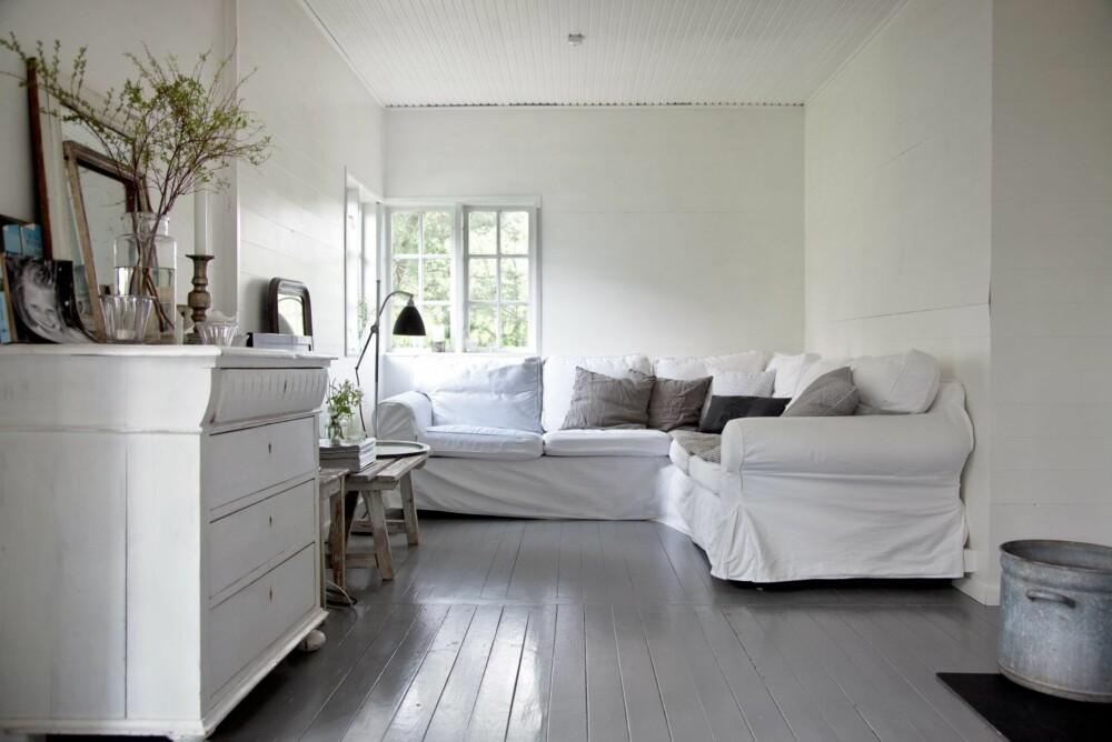 BASISFARGER: Hele huset har fått grå gulv og hvite tak og vegger i basisfargene i uttrykket som Tine K er spesielt kjent for. Mange vil  kalle stilen nordisk. Den hvite sofaen fra Ikea har avtagbart bomullstrekk, så den tåler røff bruk. Den brukes både til pur  avslapning og som filmkrok.