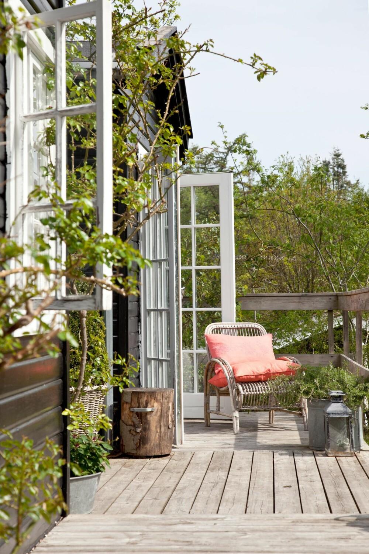 EN PLASS I SOLEN: Langs huset står flere små sittegrupper, og det fins også en plass i solen under klatrerosen, som blomstrer fra juni til frosten kommer. Møbler, tepper og puter fra Tine K Home.