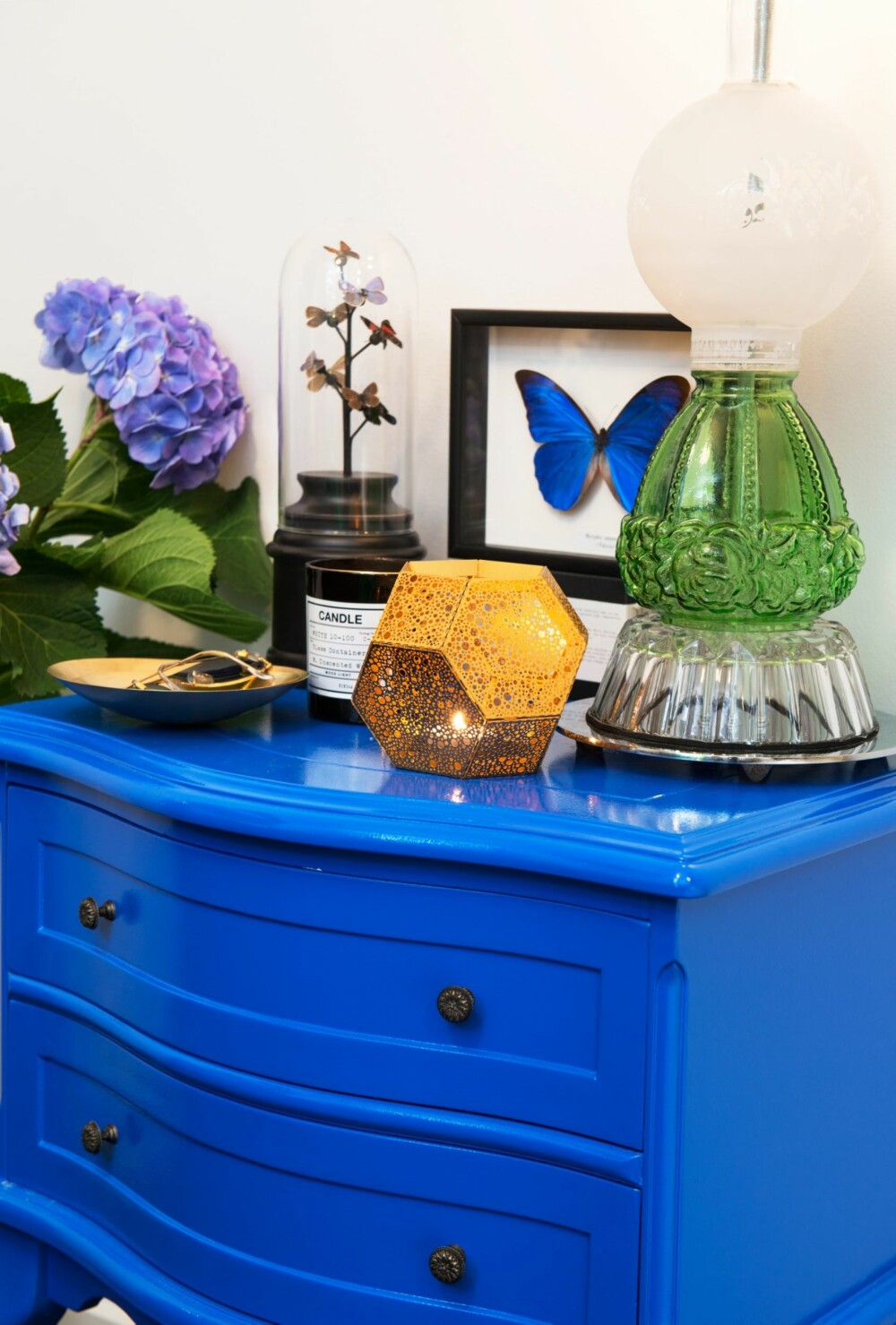 SYSTEM PÅ PYNTEN: Interiørarkitekten og Hildegunn fant en brukt kommode på Finn, som ble malt blå, fargekode NCS S 2565-R80B blank lakk. Enkle pyntegjenstander, en sommerfugl i samme blånyanse, en glasslampe med runde former og en Tom Dixon telysholder i kobber, utgjør et dynamisk stilleben mot den hvite veggen. Tingene er kjøpt hos Eske.