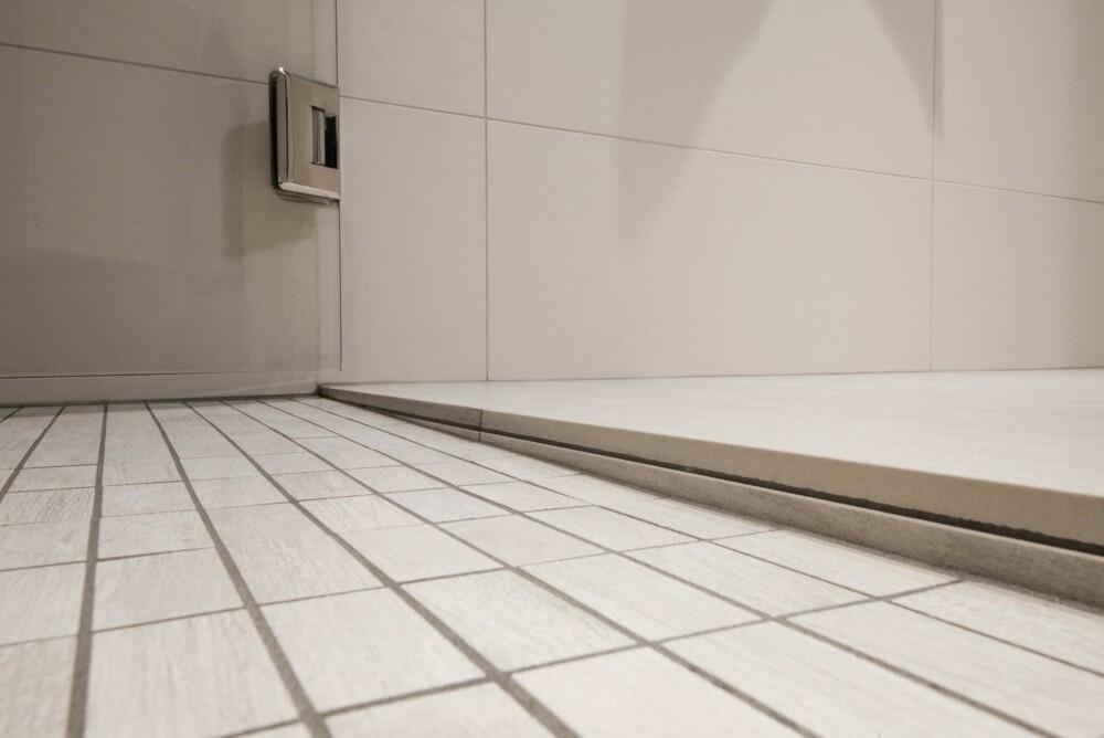 UNIDRAIN SLUK: I denne dusjen er det laget fall i en retning mot Unidrain-sluket. Håndverker har senket området  litt ned fra resten av gulvet med et fall mot den ene enden av dusjsonen.