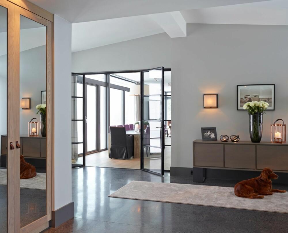 GRÅSONER: Huset har store proporsjoner, med sjenerøse vinduer som går fra gulv til tak. Gråfargen på veggene heter Pavillion Grey og er fra Farrow & Ball. Skjenken er fra PH Collection, lykten fra Blomsteroasen og de øvrige lampene fra belgiske Davidts Lighting.