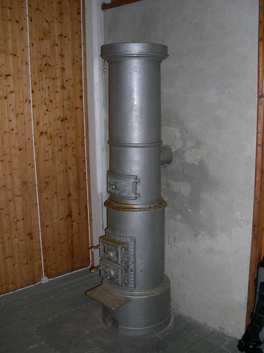 """RUNDBRENNER: De aller fleste sylinderovner/ rund magasinovn - eller """"""""rundbrenner"""""""" for ved, koks og kull er produsert før 1920 og ikke etter 1940. Denne er fra Dønnesfjord kirke."""