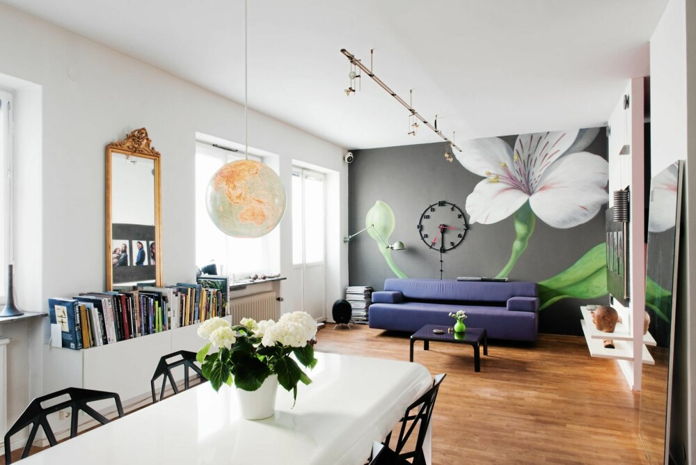 KJEMPEBLOMST OG KNALLFARGER: Selv om hvite vegger reflekterer lyset best, trenger ikke alle boligens flater være hvite. Blomsten som dekker hele den ene kortveggen er malt rett på muren, og tilfører både liv og dybde.  Det digre speilet på gulvet forsterker lysinnfallet og utvider romfølelsen.