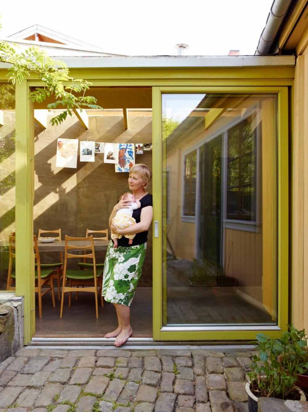SENTRALT PLASSERT: Fra terskelen til den brostensbelagte uteplassen har Ane Senstad Guldahl kontakt både med kjøkkenet i tilbygget og med det gamle huset. Det er her trafikken er størst.