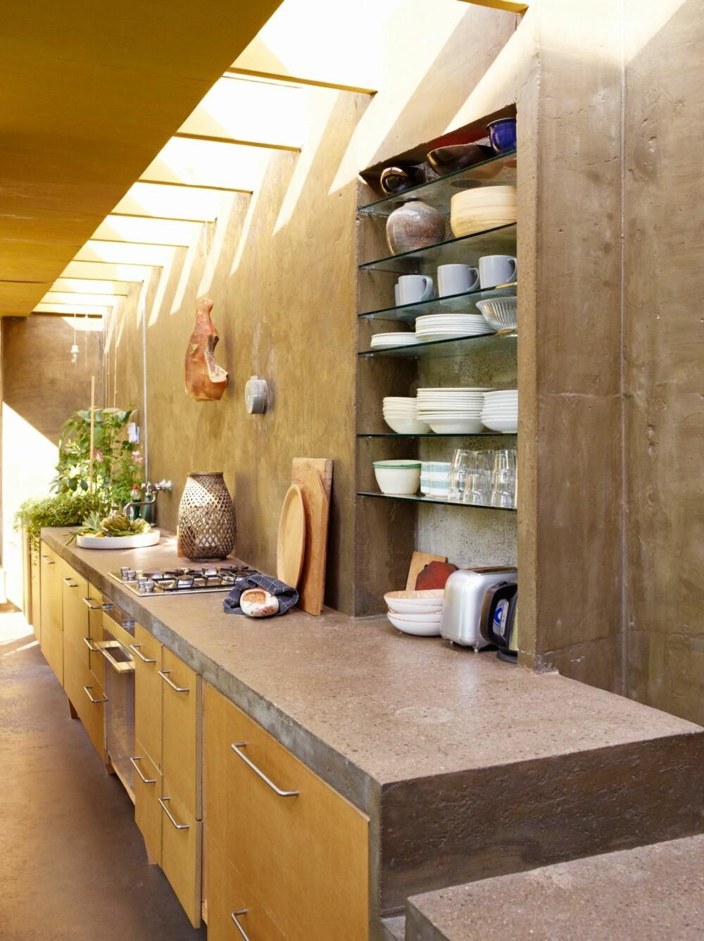INNEKJØKKEN MED UTEFØLELSE:  Overlyset gir en fornemmelse av å befinne seg utendørs. De åpne hyllene er tilpasset familiens kjøkkenartikler slik at volumet utnyttes maksimalt.