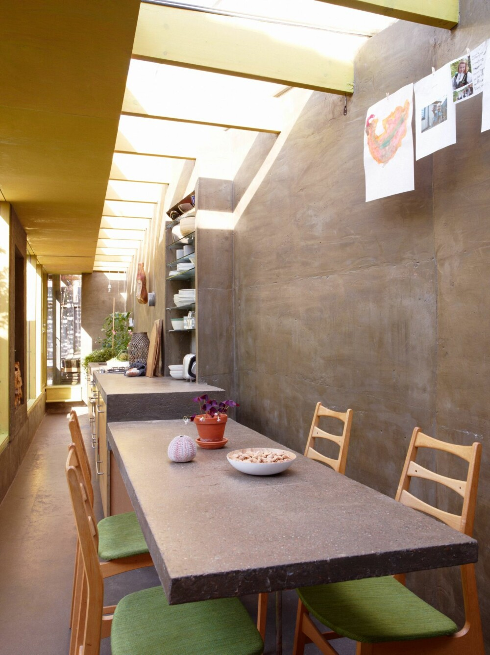 GJENNOMTENKT BETONGSTRUKTUR: Den lange benken er både spisebord, kjøkkenbenk og plantegrop i ett grep. All innredning er spesialtilpasset. og integrert i konstruksjonen.