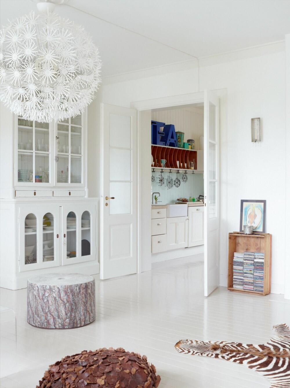 KONTAKT MED KJØKKENET: Fra stuen har man god kontakt med kjøkkenet. Vitrineskapet er kjøpt på finn.no, puffen med furumønster er fra Ygg&lyng, mens taklampen er fra Ikea.