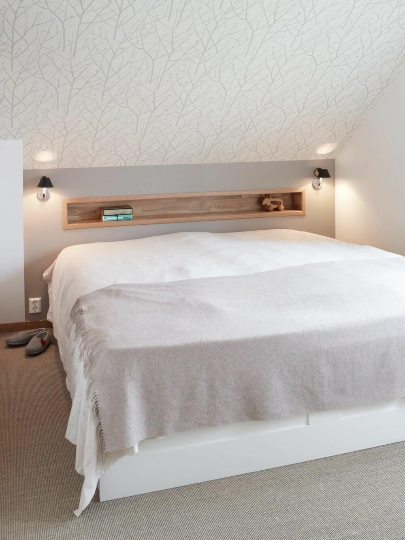 AVLANG INNFELLING. Sengen er plassert under skråtaket. For å spare plass er nattbordfunksjonen laget som en nisje i eik over sengen. Skråtaket har fått nøytral tapet. Gulvet er kledd med sisal fra Teppabo. Nattbordlamper Tolomeo Micro Faretto fra Artemide.