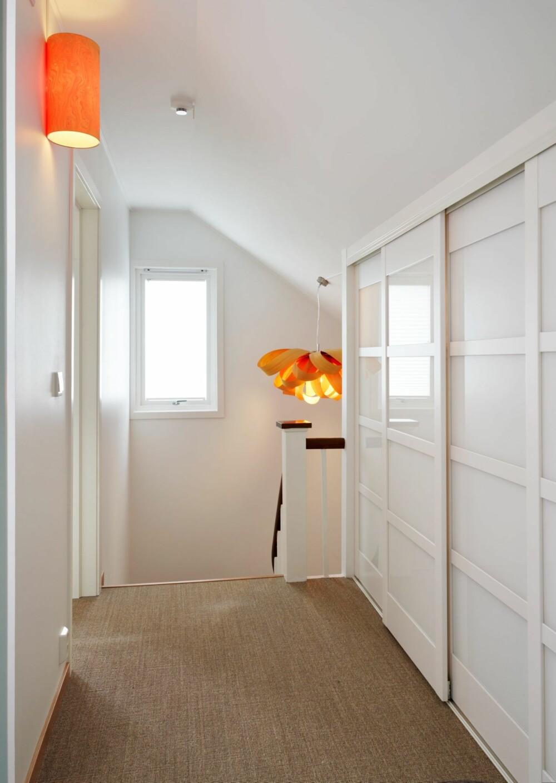 OPPTRAPPET. Lampene i trappen kommer fra Lzf, en kostbar med heldig investering, mener beboerne. Garderobe fra Langlo dekker hele den ene veggen. Gelenderet er beholdt som det var, mens gangen er malt i klassisk hvit S0500-N. Fargen er videreført ned til første etasje. Gulv i sisal.