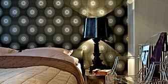 STJERNER OG AKRYLPLAST: Det blåsvarte stjernetapetet er fra Squee. Stol, lampe og nattbord er tilvirket i akrylglass og produseres av italienske Kartell.