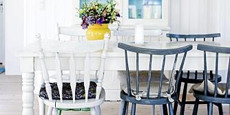 TREND I INTERIØRET: Spisestuen er lys og luftig med hvite vegger og tak, og et lyst tregulv. Både vitrineskapet og spisebordet går i ett med det hvite rommet. Beboerne har heller valgt å tilføre fargene i detaljene. Det blå glasset i vitrineskapet tar opp fargen fra de blå kjøkkenstolene, og en gul vase med fargerike blomster er plassert på bordet.