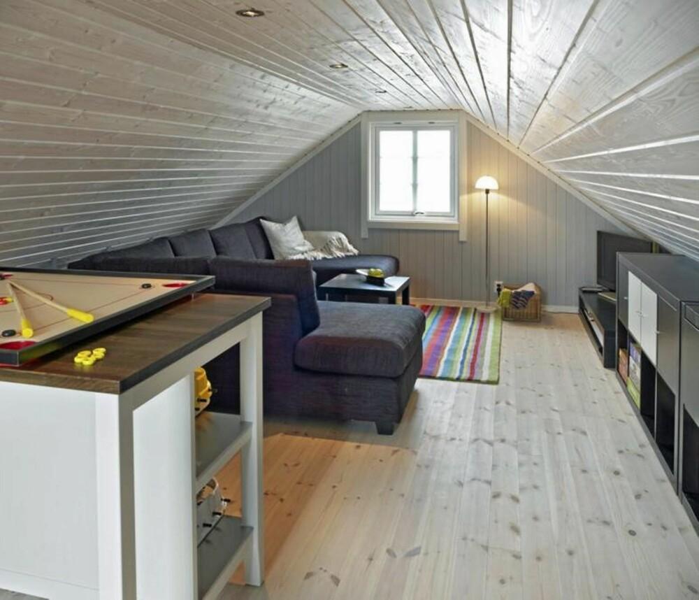 LOFT OVER GARASJE: Loftet på denne store garasjen har blitt til et lekkert oppholdsrom, med kun 1.87 meter under taket. Plassen under skråtaket er godt utnyttet, også bak sofaen er det oppbevaringshyller. Furugulvet fra Siljan er hvitvokset.
