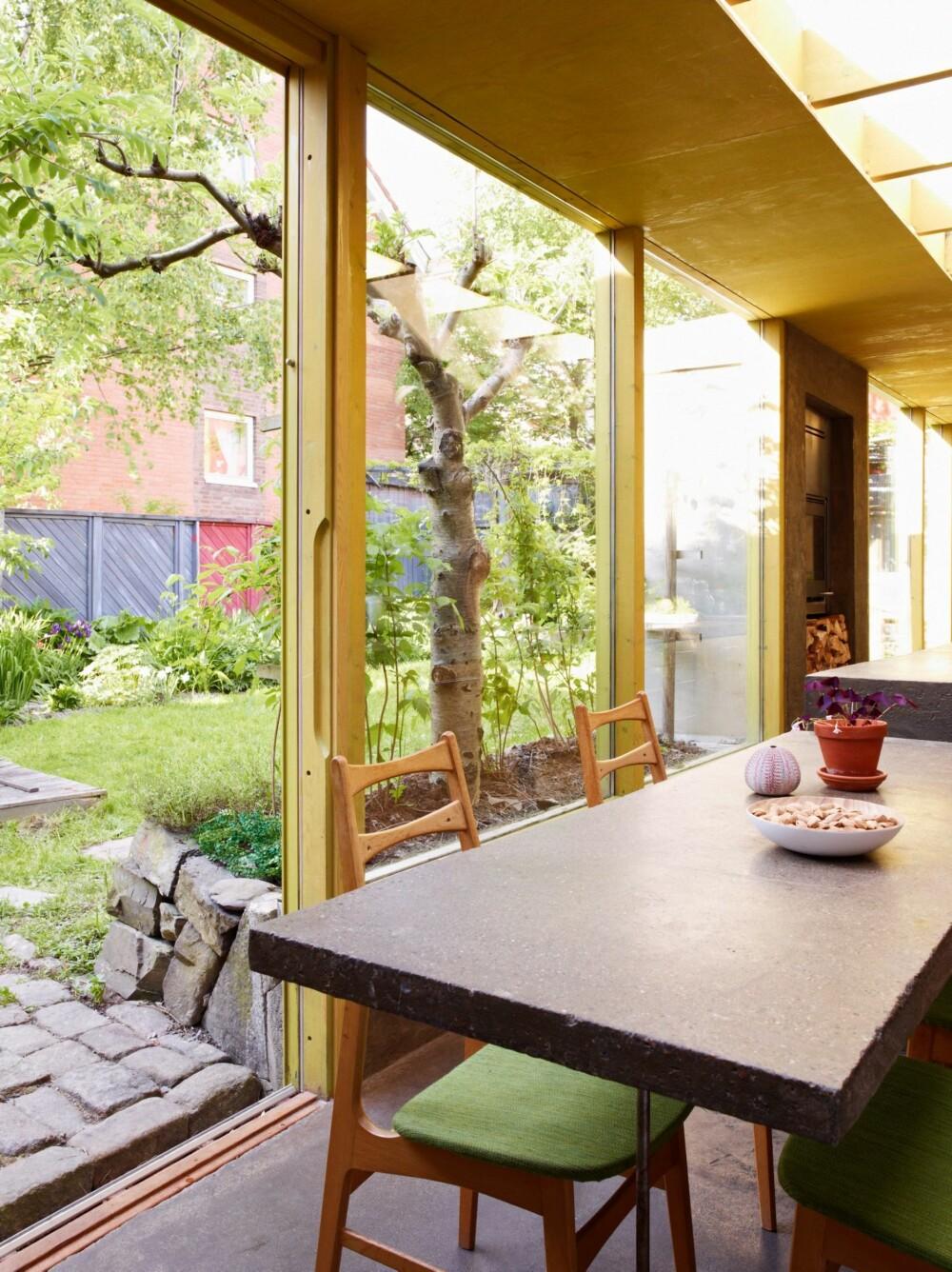 UTSYN MOT HAGEN: Store glassflater bidrar til at hagen integreres i boligen, som et ekstra rom. Stoler i tre med grønt trekk gjør at innerommet harmonerer enda bedre med hagen utenfor.