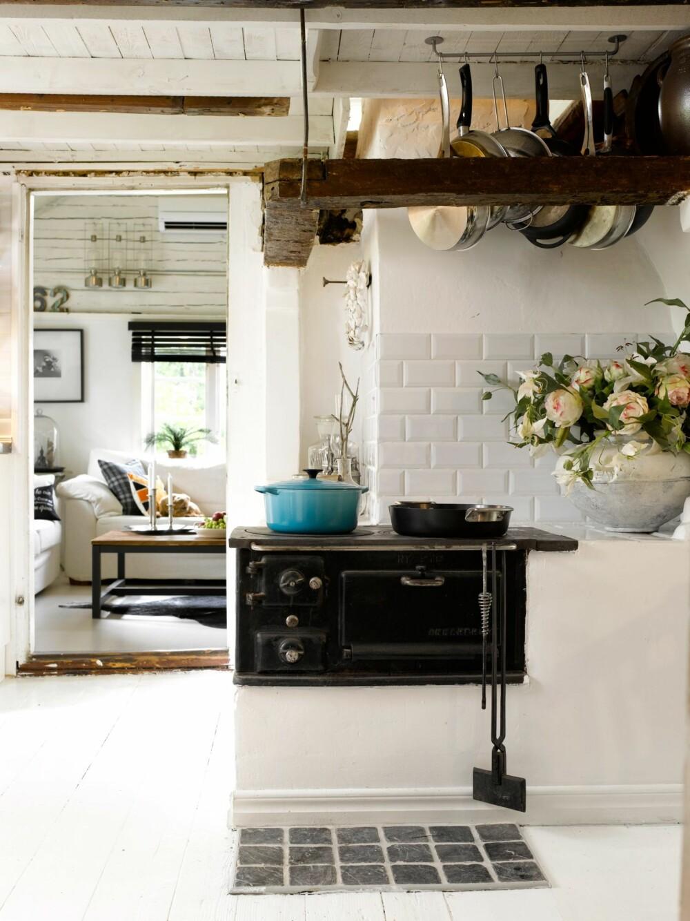"""NOSTALGISK OVN: Bevar eller sett inn en gammel  ovn for et autentisk utrykk. Den gamle ovnen på bildet her er fortsatt i bruk, og stammer fra 1940/50-tallet. En tøff, turkis jerngryte er et friskt innslag, og et viktig element for å """"få stilen"""" er å henge opp gryter eller annet kjøkkenredskap synlig."""