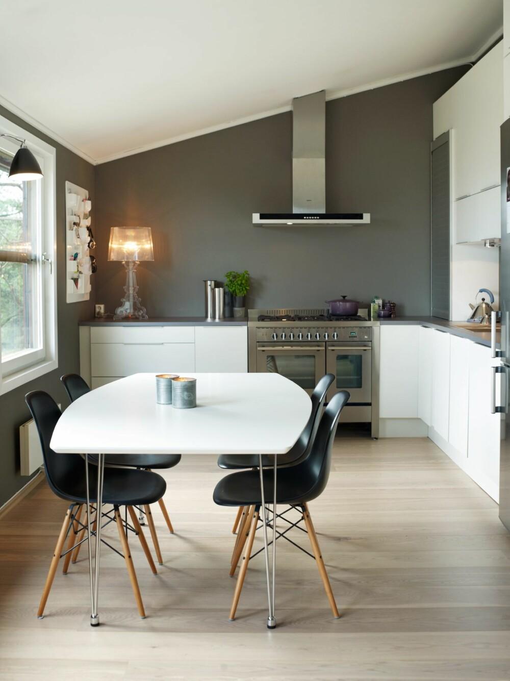 """STILRENT: Alle vegger er malt i grått, mens innredningen er hvit. Lampen på kjøkkenbenken myker opp det stramme utrykket. Ønsker du et mere """"bohemsk"""" preg kan du innrede med møbler og lamper i denne stilen."""