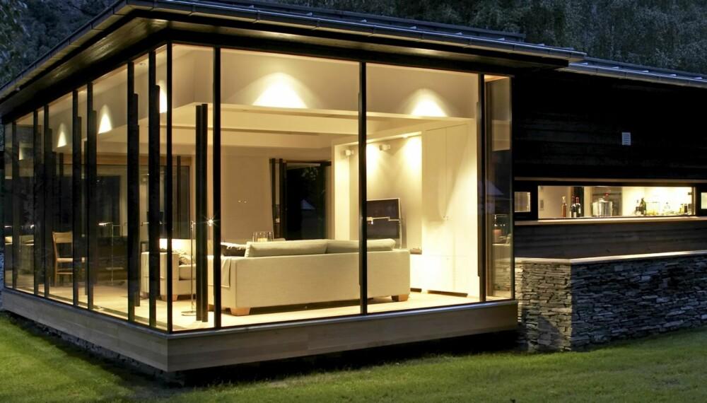 UTSTRÅLING: Den belyste stuen er innbydende og har fin lyssetting. Vil du unngå svarte hull som stjeler lys, kan du trekke for vinduene om kvelden.