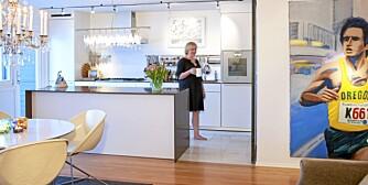 SPREKT KJØKKENINNSLAG. Et stort maleri av Anders Kjær dominerer på den ene kjøkkenveggen. Line Norling har fliser i matlagingssonen mens resten av kjøkkenet har gulvpanel i heltre rødeik. Innredning fra Bulthaup. Lampe Cullula over kjøkkenøya.