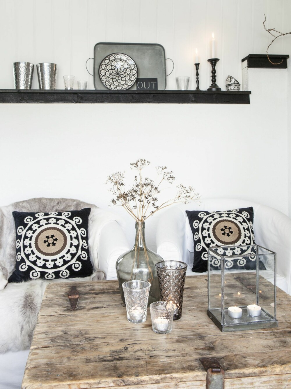 GOD STEMNING: Stolene fra Ikea har fått myke skinn og dekorative puter fra Princess. En vase med tørre vekster fra hagen er dekorativ pynt i vinterhalvåret, sammen med levende lys i lykter fra House Doctor og Tine K Home. En hylle på veggen holder flere lys og fin dekor.