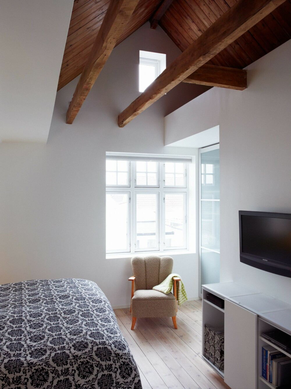 VARMT OG KJØLIG: Etter at taket ble revet kom takmønet til sin rett som et arkitektonisk innslag på soverommet. Det originale treverket gir varme til det ellers kjølige rommet. Stolen er kjøpt hos Fretex.