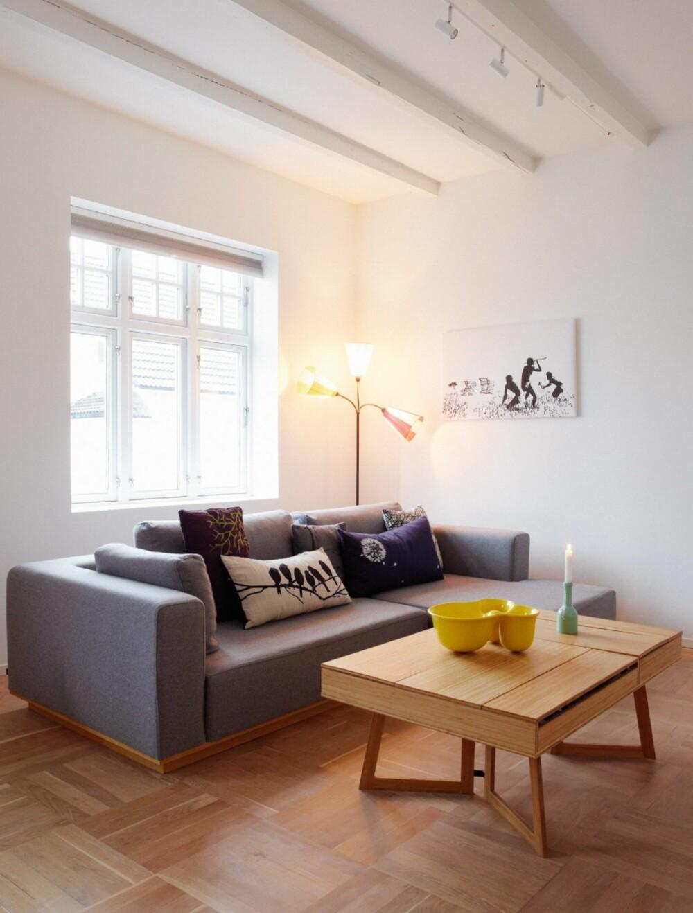 RENE GIPSFLATER: De rene gipsflatene fremhever bjelkene og det originale, skjeve tregulvet. Putene i sofaen er fra Rom for mer, Living og Bolia, den grønne lysestaken er fra Ting og den gule Ole Jensen-bollen er fra Muuto. Bildet er en Banksy-kopi som selges på eBay. Tivolilampen er vintage, og bord og sofa er fra Bolia.